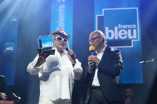"""Un trophée spécial """"Artiste scène de l'année 2016"""" a été remis à Michel Polnareff ici aux côtés d'Eric Sorek, directeur des programmes du réseau France Bleu © Radio France / M. Genon"""