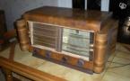 Un vieux poste de radio qui trône sur la table d'une cuisine.